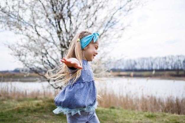 Adorable petite fille jouant dans un jardin de pommiers en fleurs à la chasse aux œufs de pâques, courant et souriant. enfant dans un verger de printemps avec des fleurs de cerisier.