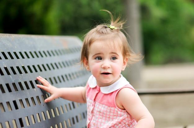 Adorable petite fille jouant dans un parc urbain