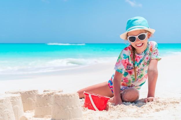 Adorable petite fille jouant avec des jouets de plage pendant des vacances tropicales
