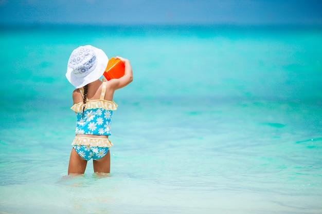 Adorable petite fille jouant avec des jouets de plage sur la plage tropicale blanche