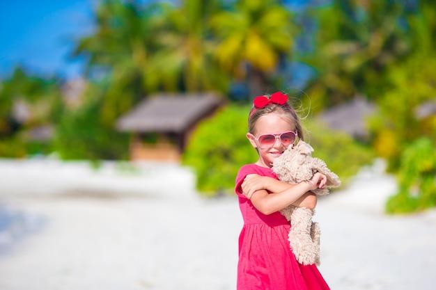 Adorable petite fille jouant avec des peluches sur la plage