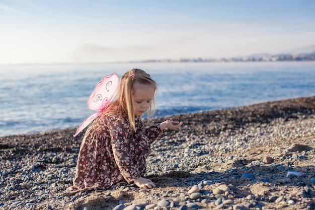 Adorable petite fille jouant sur la plage en une journée ensoleillée d'hiver