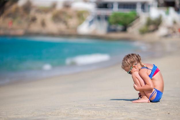 Adorable petite fille jouant à la plage pendant des vacances européennes
