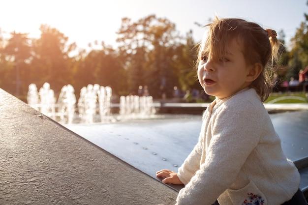 Adorable petite fille joue par une belle journée ensoleillée dans le parc. fermer