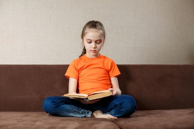Adorable petite fille lisant un livre dans sa maison