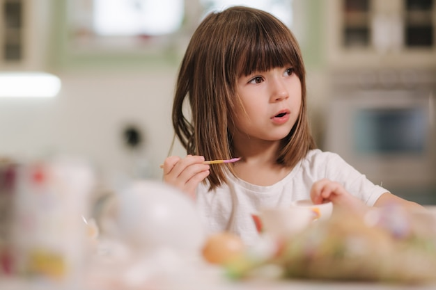 Adorable petite fille lors de l'impression d'oeufs de pâques à la maison belle fille se préparant pour pâques