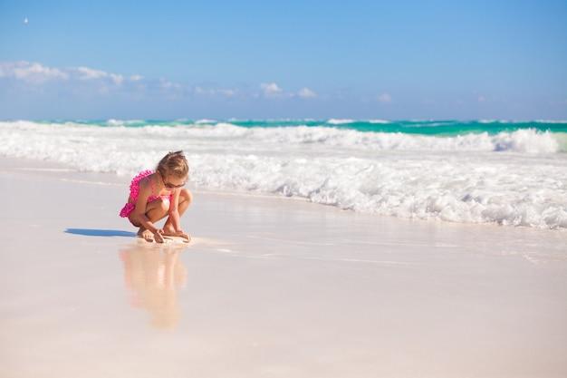 Adorable petite fille en maillot de bain à la plage tropicale des caraïbes