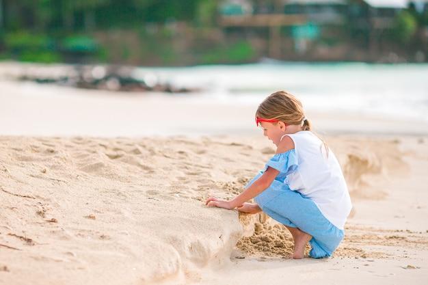 Adorable petite fille en maillot de bain à la plage tropicale