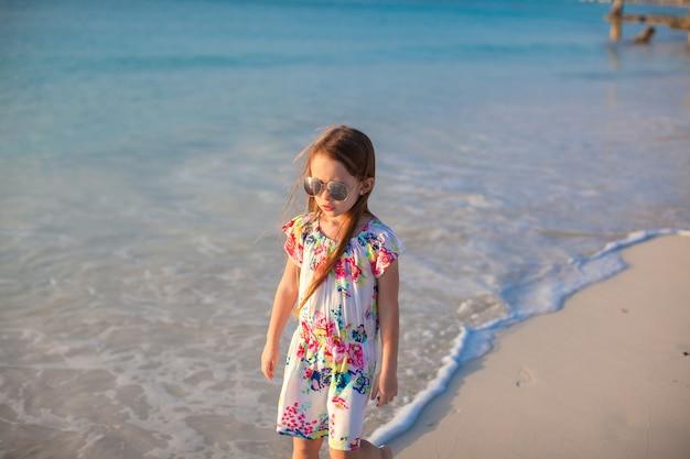 Adorable petite fille marchant sur une plage tropicale blanche