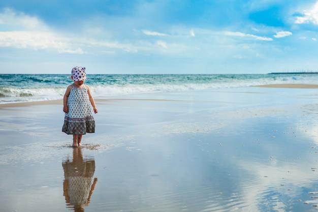 Adorable petite fille marchant sur le wateron la plage, mer méditerranée, espagne