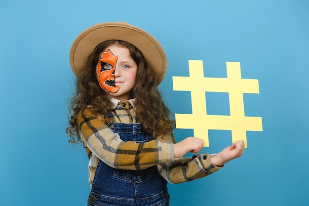 Adorable petite fille avec un masque d'halloween tenant un symbole de hashtag jaune et heureuse de regarder la caméra, montrant un signe de hachage, isolé sur fond bleu. publications à la mode sur les réseaux sociaux et concept de fête