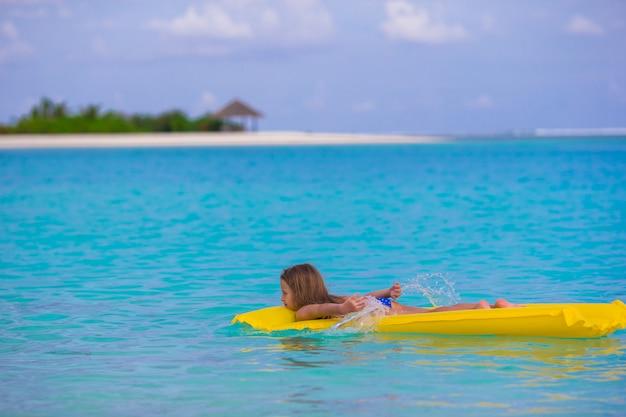 Adorable petite fille sur un matelas gonflable en mer