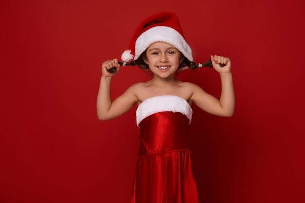 Adorable petite fille mignonne dans les vêtements du père noël pose des nattes, sourit avec un sourire joyeux à pleines dents regardant la caméra, posant sur fond rouge avec un espace de copie pour l'annonce de noël et du nouvel an