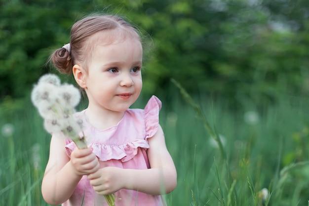 Adorable petite fille mignonne tenant un pissenlit sur un champ de fleurs de lupin