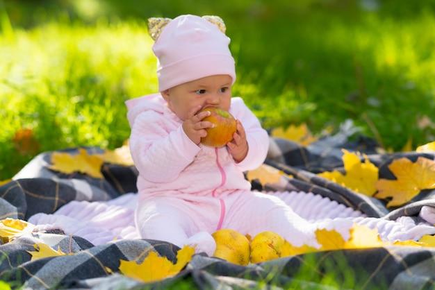 Adorable petite fille mordant une pomme fraîche alors qu'elle est assise sur une couverture sur l'herbe avec des feuilles d'automne jaunes colorées