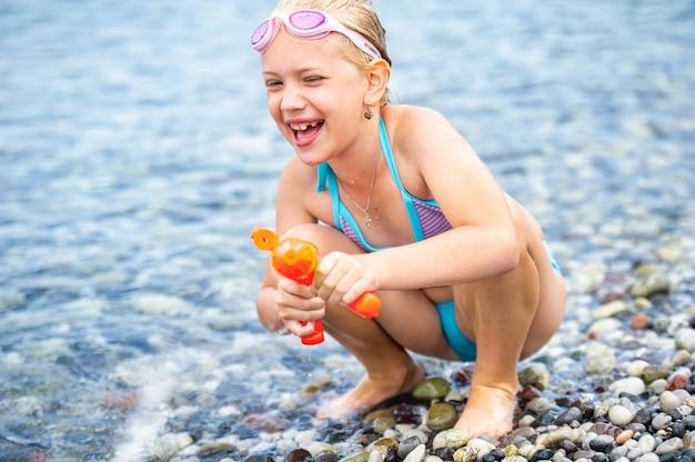 Adorable petite fille nage dans la mer et joue avec un pistolet à eau. dinde