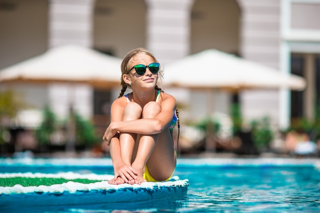 Adorable petite fille nageant à la piscine extérieure