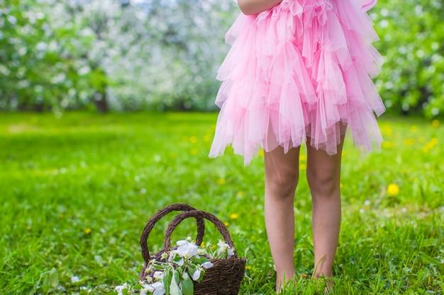 Adorable petite fille avec un panier de paille dans un jardin de pommiers en fleurs