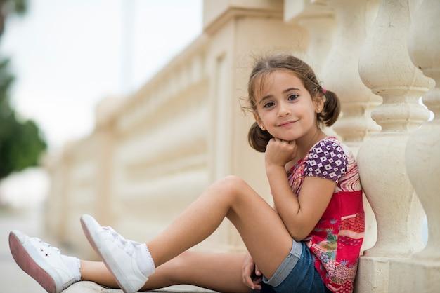 Adorable petite fille peignée avec des nattes à l'extérieur, assise sur un sol urbain.