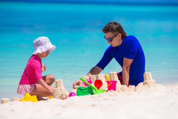 Adorable petite fille et père heureux jouant avec des jouets de plage en vacances d'été