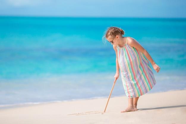 Adorable petite fille à la plage pendant les vacances d'été, dessinant sur le sable