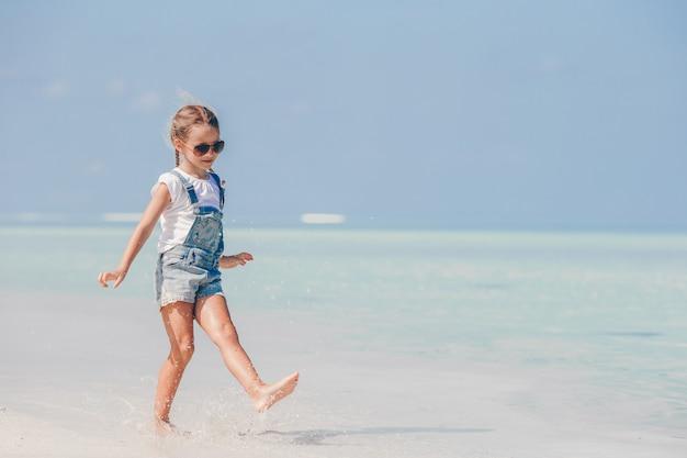 Adorable petite fille à la plage pendant les vacances d'été