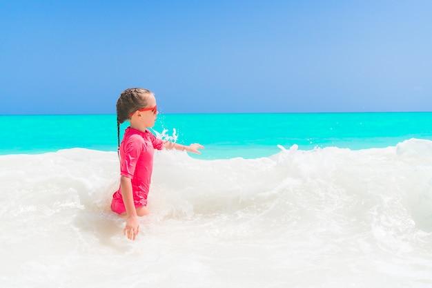 Adorable petite fille à la plage s'amuser dans l'eau