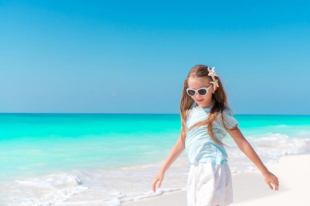Adorable petite fille sur la plage tropicale