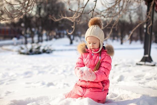 Adorable petite fille en plein air dans le parc un jour d'hiver