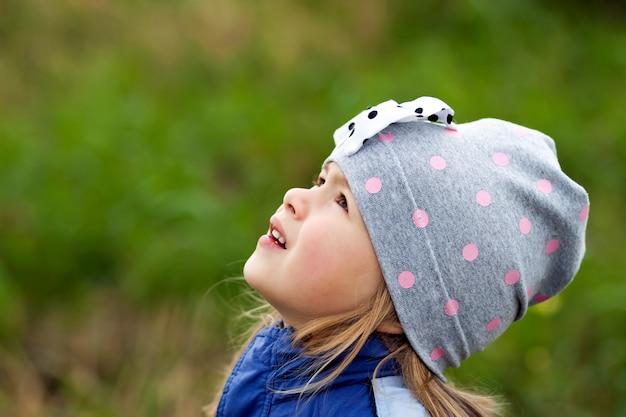 Adorable petite fille posant sur fond flou et souriant à un appareil photo. porter un manteau d'hiver et un chapeau. belle jeune fille à l'automne à l'extérieur.