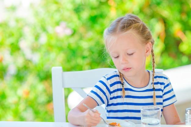 Adorable petite fille prenant son petit déjeuner au café avec vue sur la mer tôt le matin