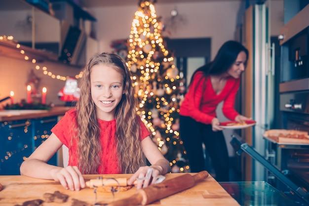 Adorable petite fille préparant des biscuits de pain d'épice de noël