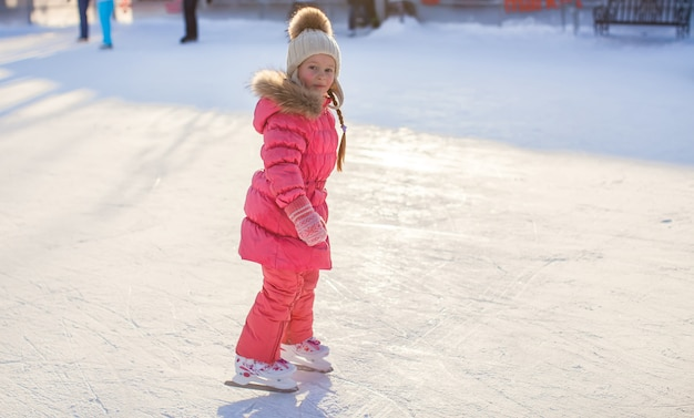 Adorable petite fille profitant du patinage à la patinoire