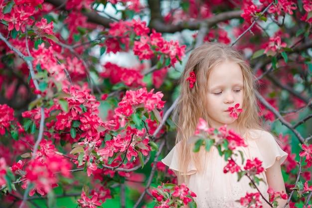 Adorable petite fille, profitant du printemps dans le jardin fleuri des pommiers