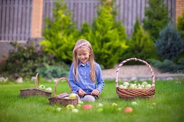 Adorable petite fille avec la récolte d'automne de tomates sur la pelouse