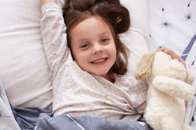 Adorable petite fille regardant directement la caméra avec une expression faciale heureuse, juste se réveiller le matin