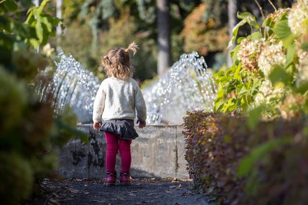 Adorable petite fille regarde la fontaine. tout-petit dans un parc avec des fontaines par une journée ensoleillée.. week-end en familleю petite fille à la recherche d'une fontaine dans le parc