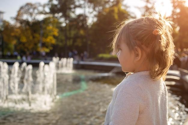 Adorable petite fille regarde les fontaines du parc dans le parc par une journée ensoleillée.
