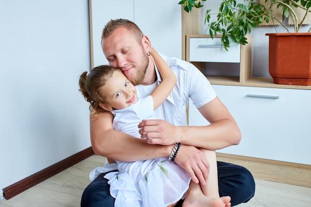 Adorable petite fille en robe blanche étreignant père aimant