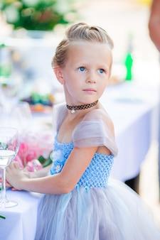 Adorable petite fille en robe incroyable lors d'une cérémonie de mariage en plein air