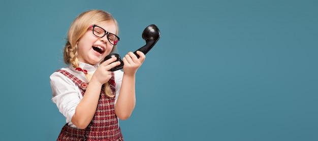 Adorable petite fille en robe rouge, une chemise blanche et lunettes tient le combiné du téléphone