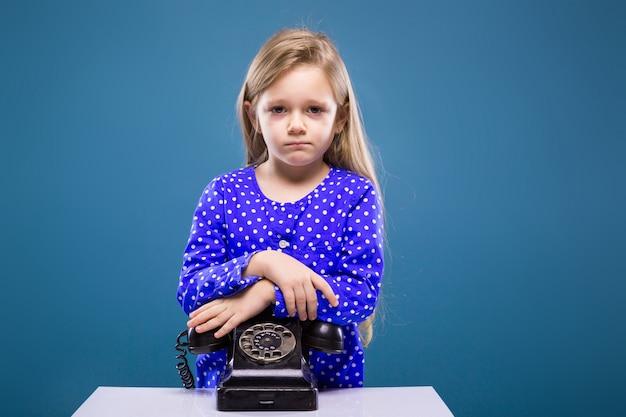 Adorable petite fille en robe violette repose sur le téléphone