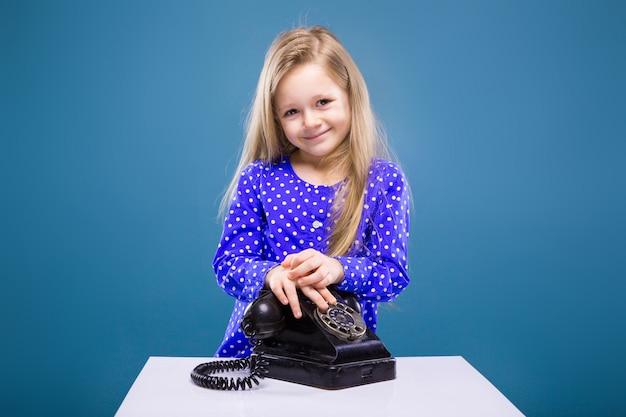 Adorable petite fille en robe violette tient le combiné du téléphone