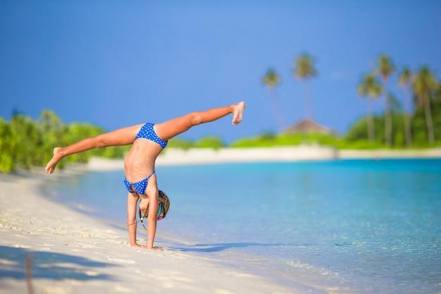 Adorable petite fille s'amusant à faire la roue sur une plage de sable blanc tropicale