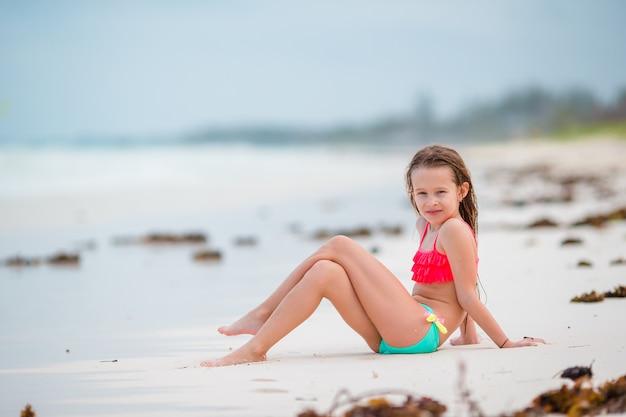 Adorable petite fille s'amuser à l'eau peu profonde sur la plage blanche