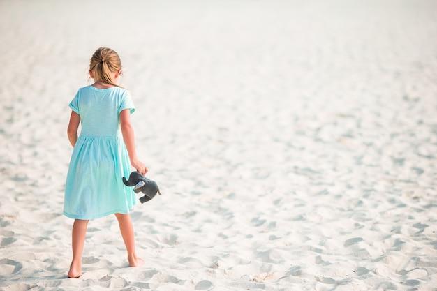 Adorable petite fille s'amuser sur la plage tropicale pendant les vacances