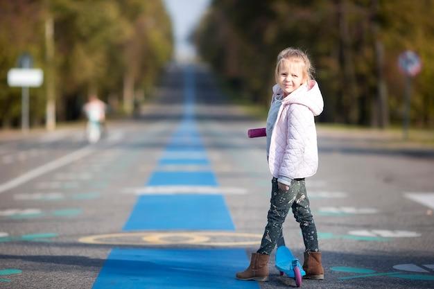 Adorable petite fille s'amuser sur le scooter en plein air