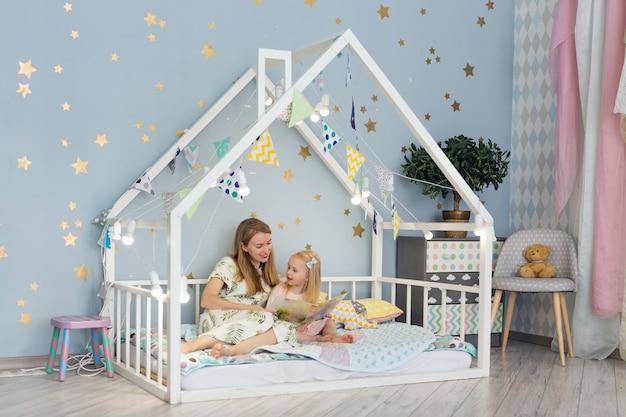 Adorable petite fille et sa jeune mère lisant un livre et souriant assis dans un lit décoré à la chambre