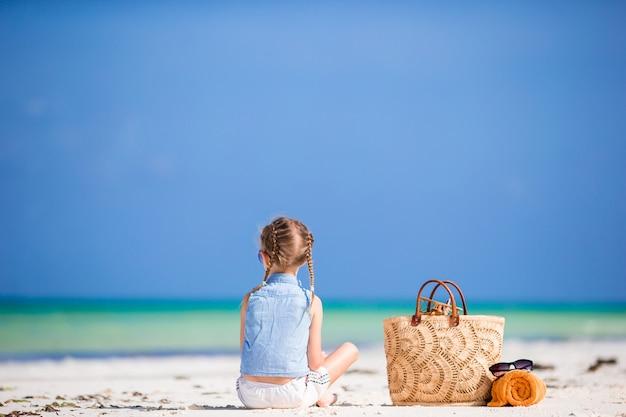 Adorable petite fille avec un sac de plage et une serviette pendant les vacances d'été