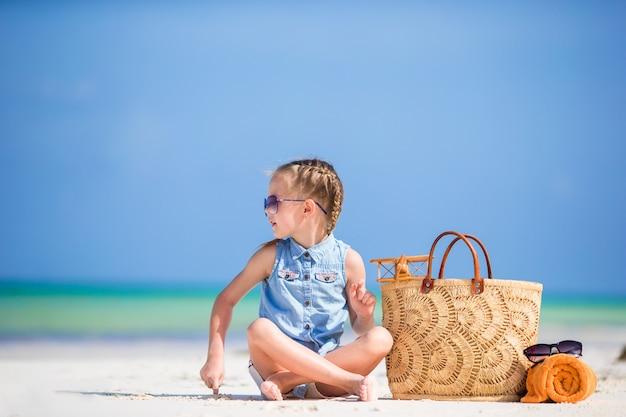 Adorable petite fille avec un sac de plage et une serviette sur la plage blanche